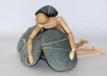 houten pop hangt lusteloos over stenen